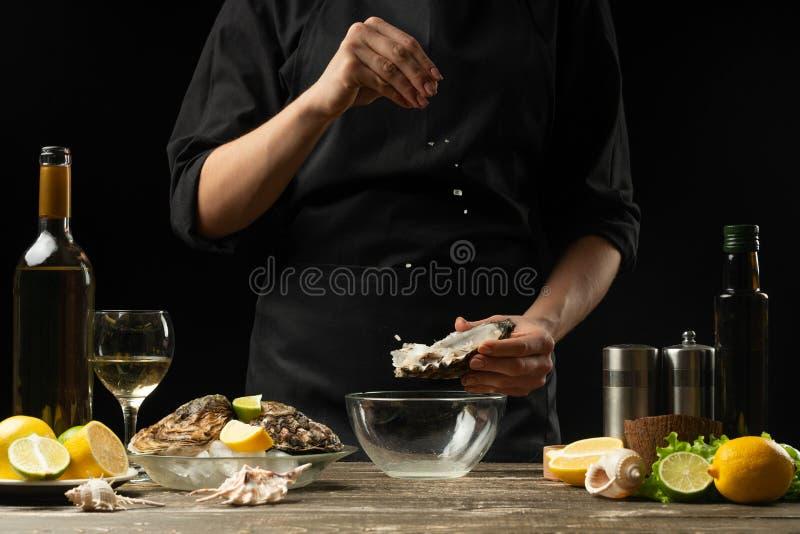 Cocinero que sala la ostra con el limón en el fondo del vino seco en un fondo oscuro, foto horizontal, menú, restaurante, italian imagenes de archivo