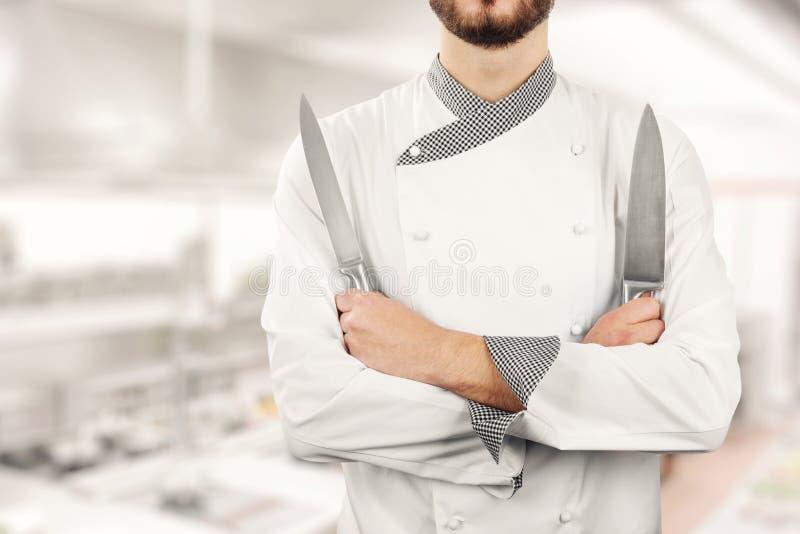 cocinero que se coloca en cocina con los cuchillos en manos fotografía de archivo libre de regalías