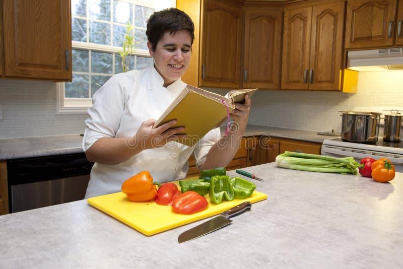 Cocinero que sonríe mirando el libro de cocina fotografía de archivo