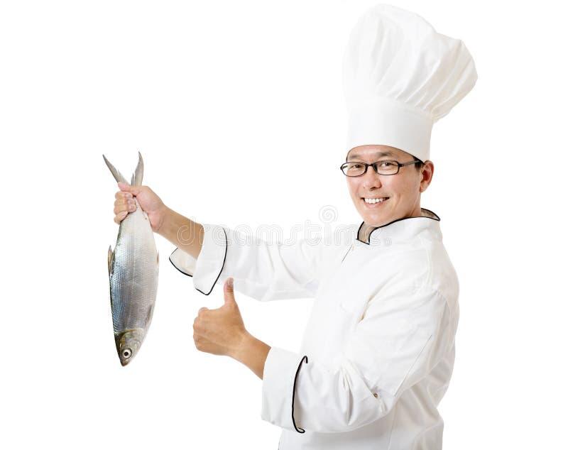 cocinero que sostiene pescados grandes aislados en blanco fotos de archivo