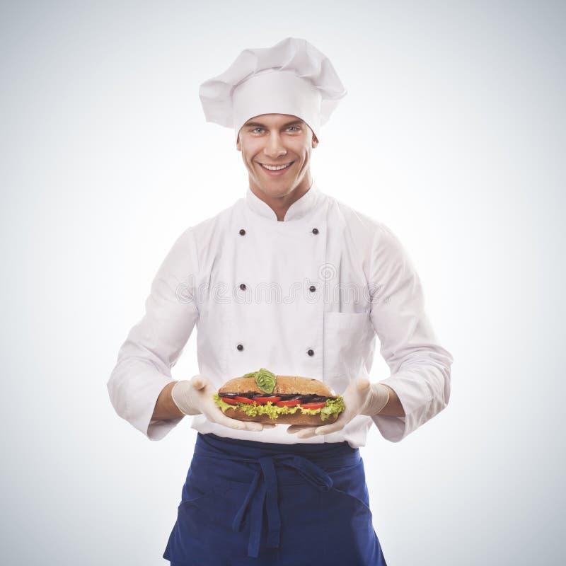 Cocinero que sostiene un bocadillo grande fotografía de archivo