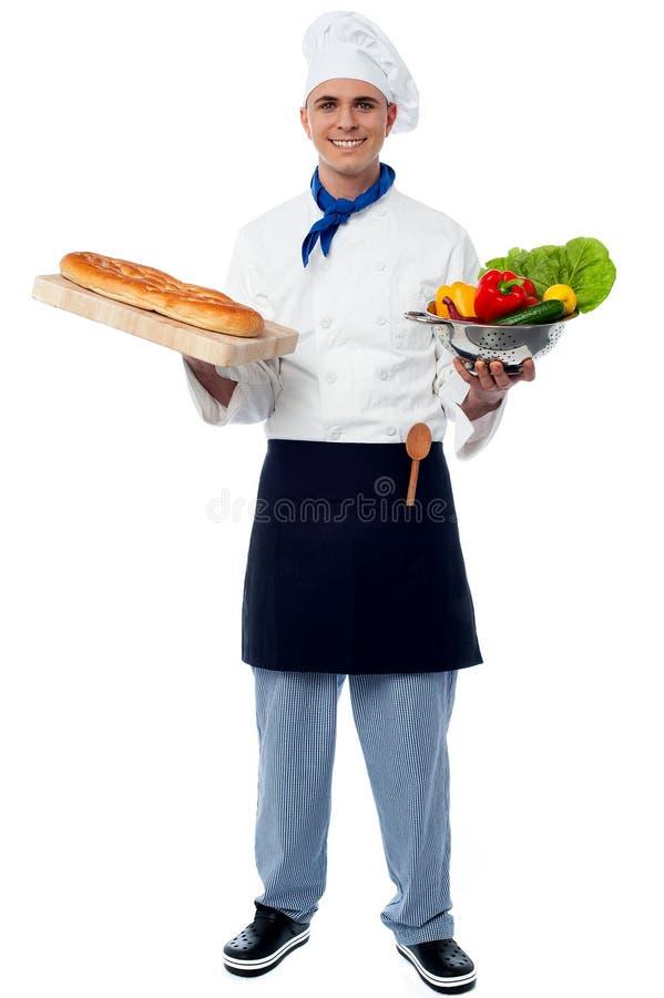 Cocinero que sostiene verduras frescas y el pan imagen de archivo