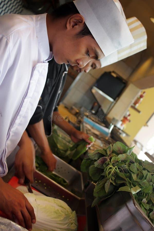 Cocinero que trabaja en la cocina imagenes de archivo