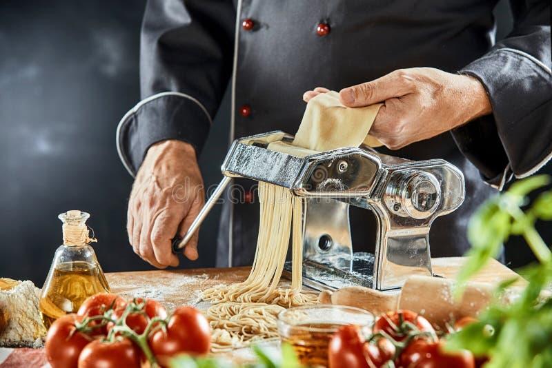 Cocinero que usa la máquina para hacer las pastas fibrosas imágenes de archivo libres de regalías