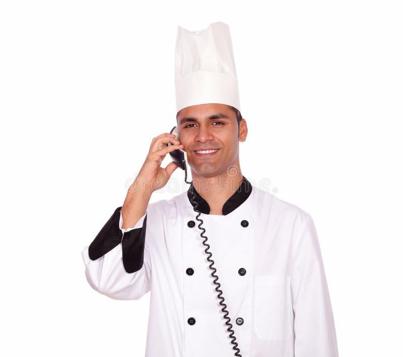 Cocinero sonriente que conversa en el teléfono mientras que se coloca imagen de archivo