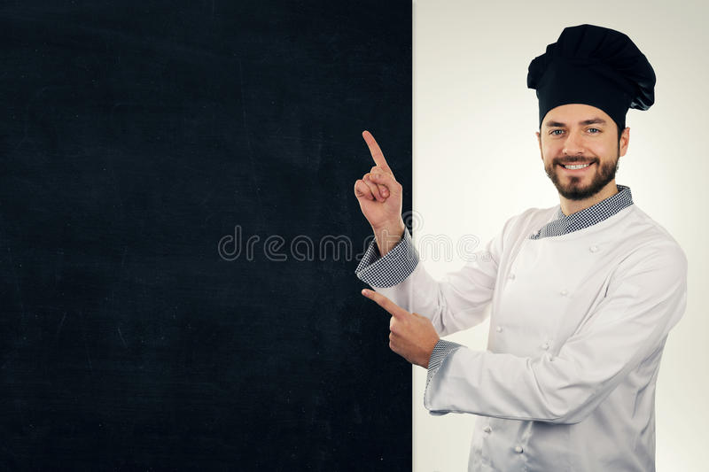 cocinero sonriente que señala en la pizarra en blanco Copie el espacio foto de archivo libre de regalías