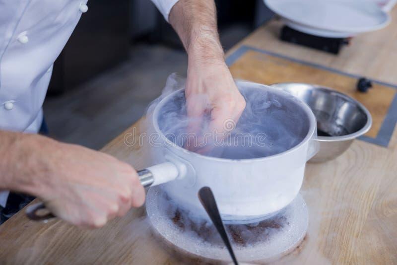 Cocinero talentoso que practica la gastronomía molecular en la cocina imagen de archivo libre de regalías