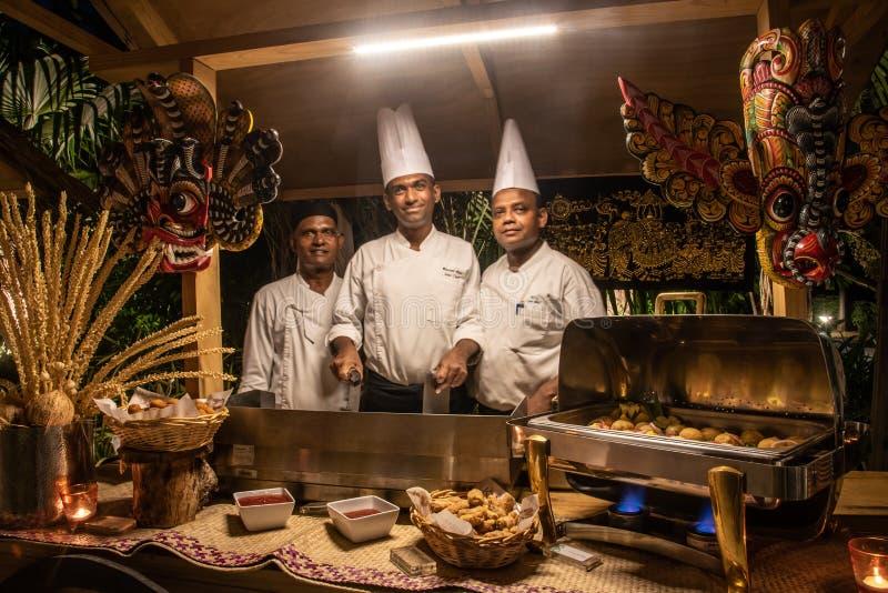 Cocineros de la cocina durante la cena internacional de la cocina al aire libre puesta en el restaurante de la isla fotografía de archivo
