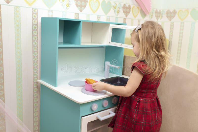 Cocineros del bebé en una estufa del juguete imagen de archivo
