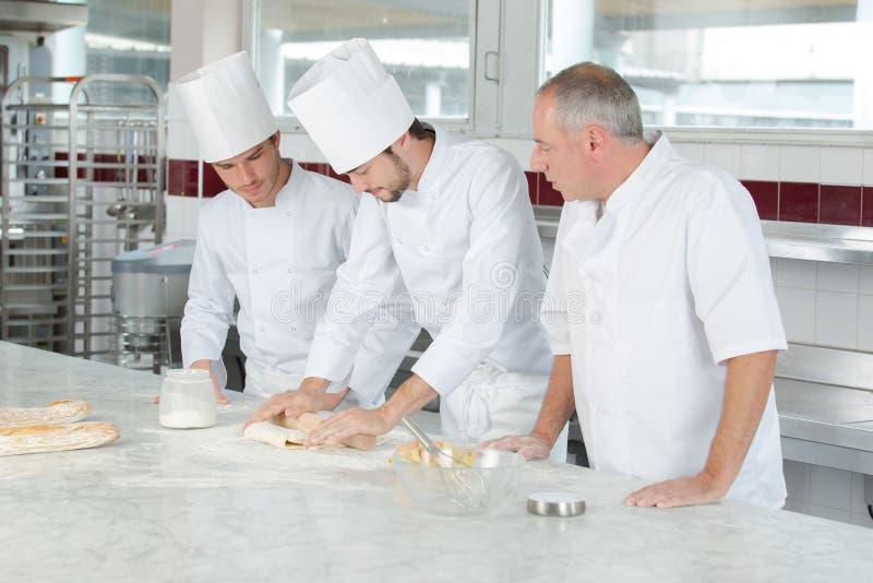Cocineros del varón y del aprendiz que trabajan en la cocina fotografía de archivo libre de regalías
