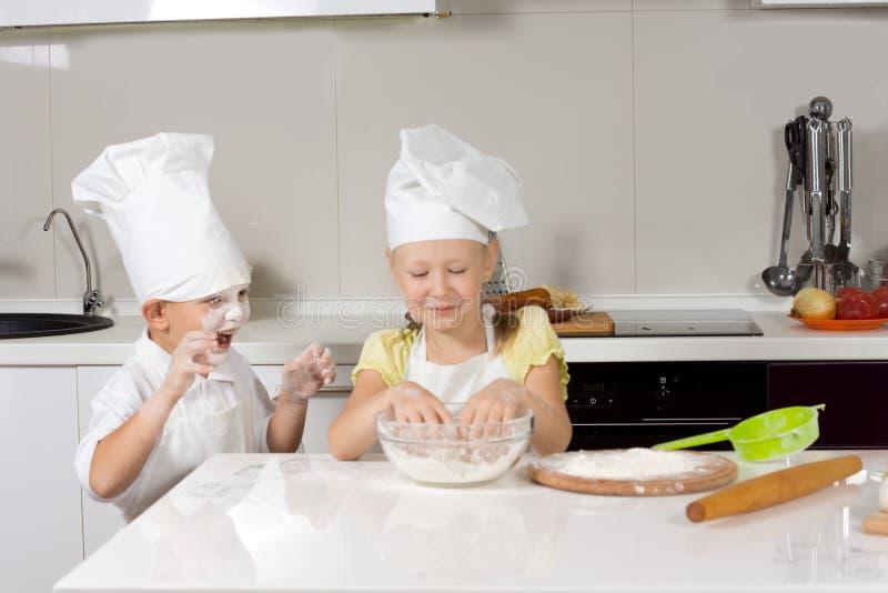 Cocineros lindos del niño que cuecen mientras que juega fotografía de archivo