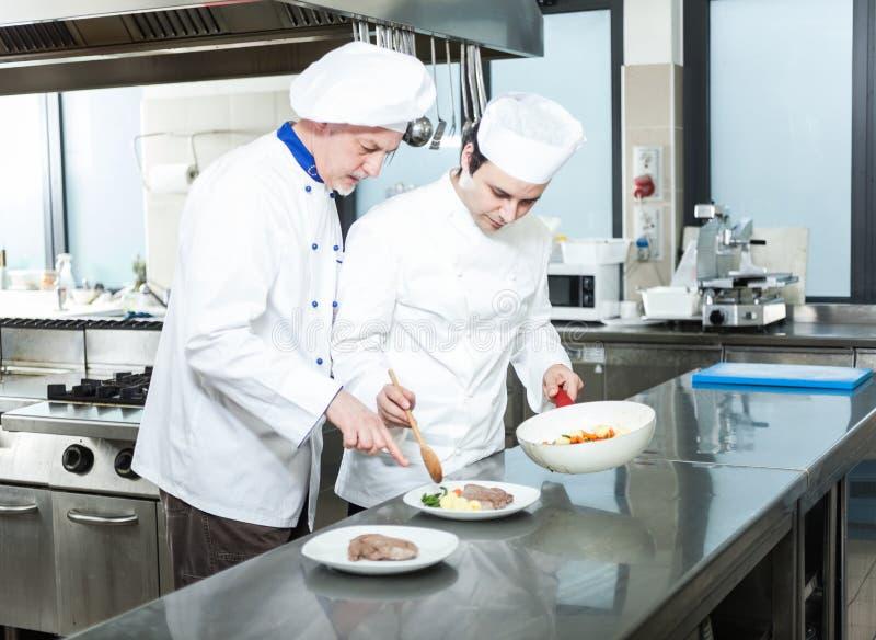 Cocineros profesionales en el trabajo fotografía de archivo