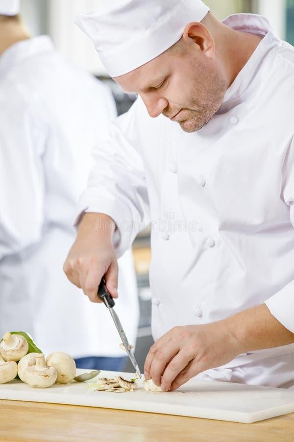 Cocineros profesionales que preparan verduras en cocina fotos de archivo