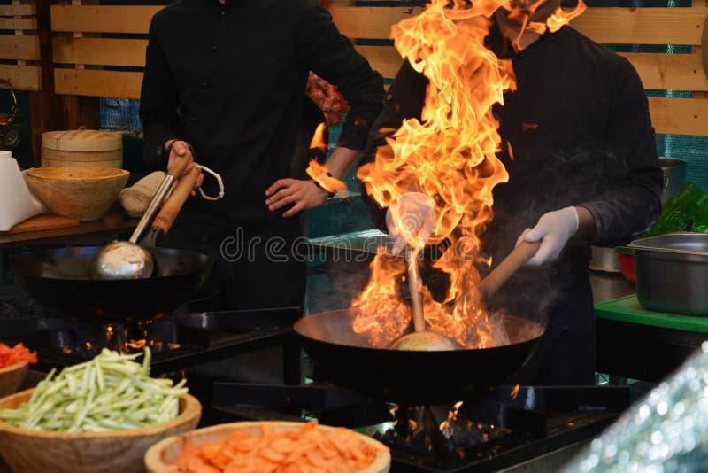 Cocineros que cocinan con la llama en un sartén imagen de archivo libre de regalías