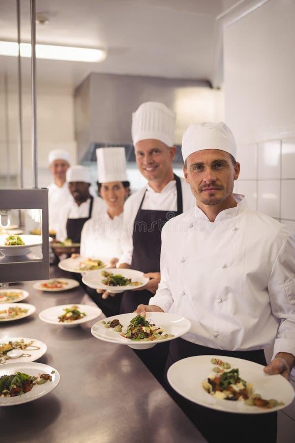 Cocineros que presentan las placas de la comida imagen de archivo libre de regalías