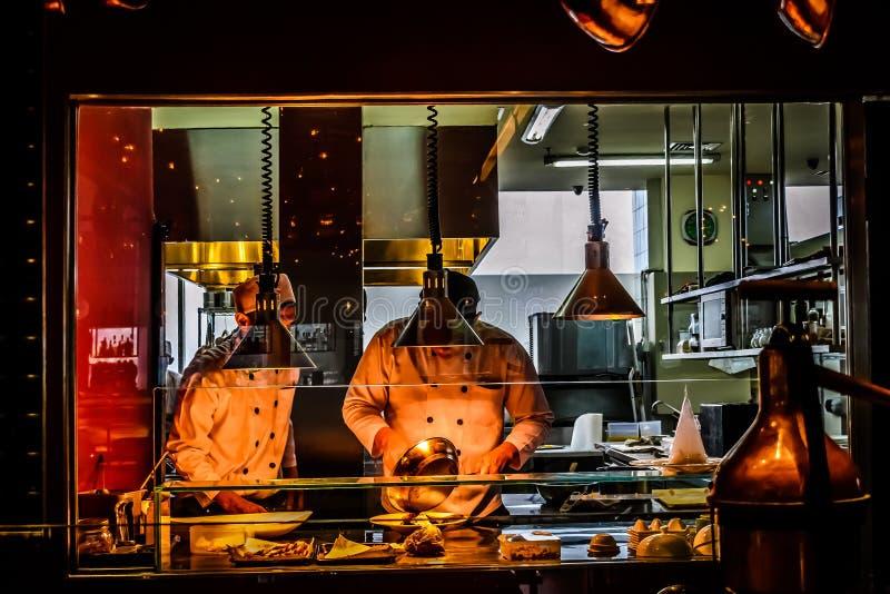 Cocineros que trabajan en cocina italiana del restaurante fotos de archivo libres de regalías