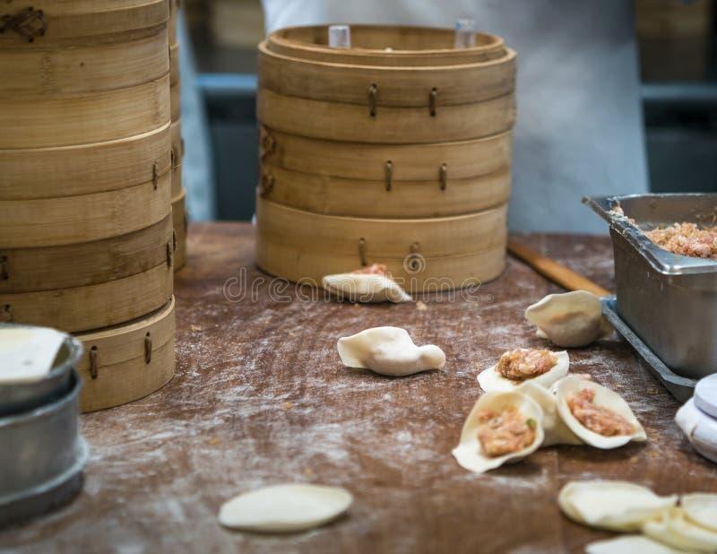 Cocineros taiwaneses del equipo que cocinan la comida tradicional Cocinero asiático que hace la bola de masa hervida Taiwán imagen de archivo libre de regalías