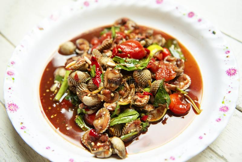 Cockles salad - Hot and spicy shellfish blood cockles salad mix vegetable tomato herb and spices thai style food royalty free stock photos