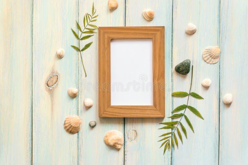 Cockleshells, folhas secadas, seixos, quadro em um fundo de madeira do vintage Configuração lisa, vista superior, espaço da cópia imagens de stock royalty free