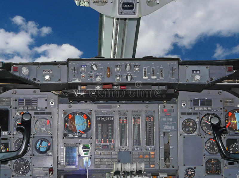 Cockpit. A jet aircraft cockpit with a blue sky stock photo