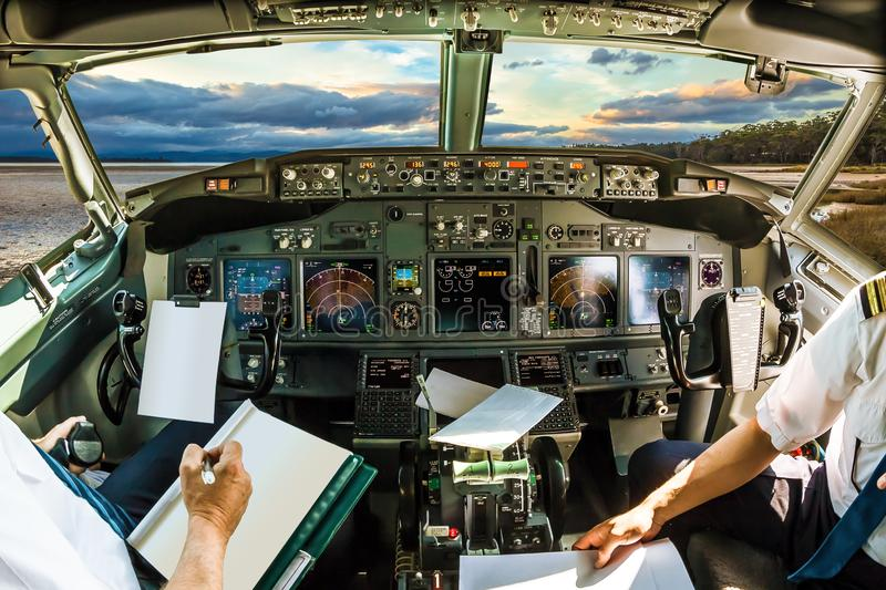 Cockpit at sundown. Cockpit and board of an airplane at sundown, with pilots arms and blank white papers for copy space royalty free stock photo