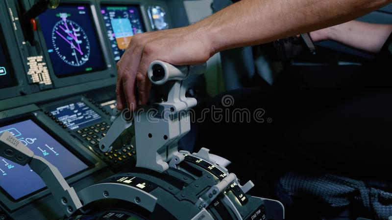 Pilot holding hand on the thrust lever handle for engine control of airliner. Cockpit cabin door inside. Pilot holding hand on the thrust lever handle for royalty free stock photography