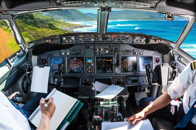 Cockpit in Cape Peninsula. Cockpit and board of an airplane flying in Misty Cliffs, Cape Peninsula in South Africa, with pilots arms and blank white papers for stock image