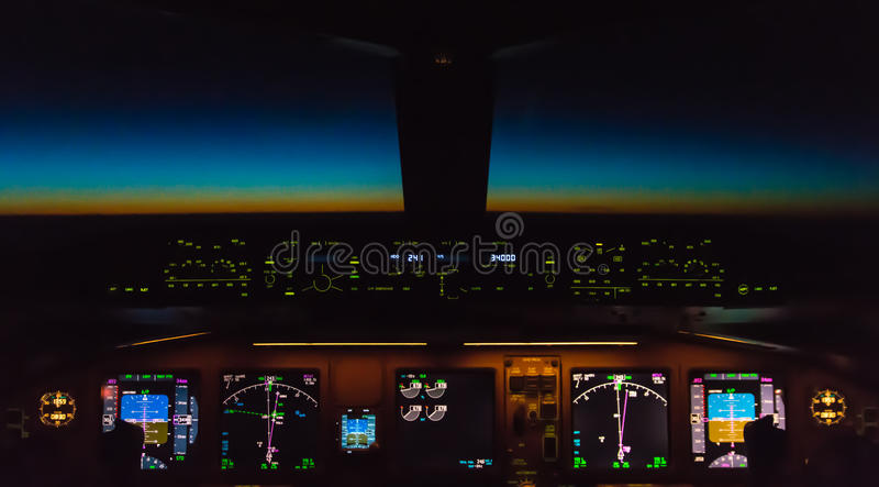 Cockpit night Controls. Cockpit controls at night, sun coming up behind the horizon stock photo