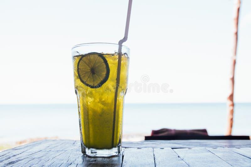 Cocktai com gelo no vidro está na tabela de madeira no mar do azul do fundo fotografia de stock