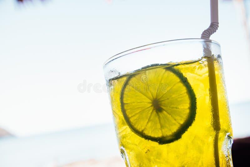 Cocktai con ghiaccio in vetro sta sulla tavola di legno sul mare del blu del fondo immagini stock