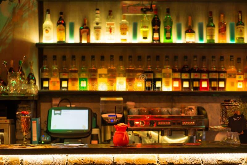 Cocktail à la barre dans la tache floue de fond des bouteilles d'alcool photographie stock