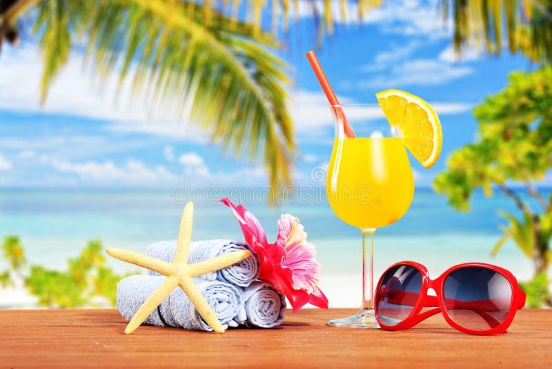 Cocktail alaranjado e outros acessórios do verão em uma tabela com amigo fotos de stock