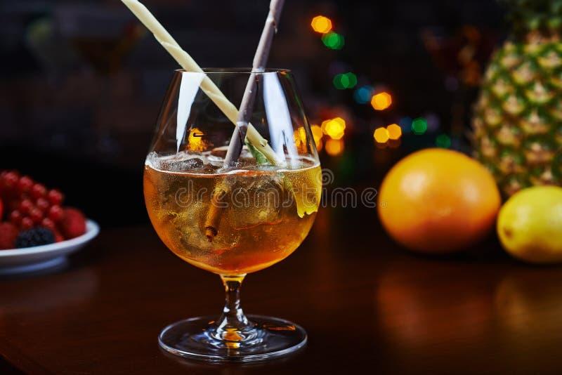 Cocktail alcoólico forte brilhante com uma decoração criativa de varas do chocolate e de cubos de gelo em uma tabela em um restau foto de stock royalty free