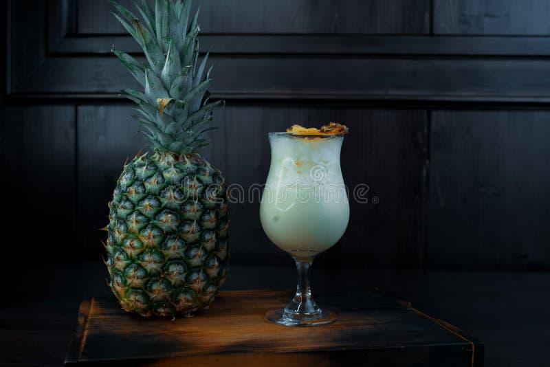Cocktail alcoólico leitoso branco doce com suco com cubos e tônico de gelo com vodca em uma tabela marrom perto de um abacaxi fre fotografia de stock royalty free