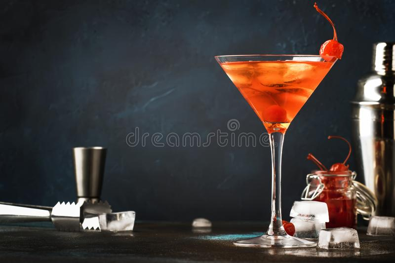 Cocktail alco?lico cl?ssico Manhattan com bourbon, a cereja vermelha do vemuth, a amarga, do gelo e do cocktail no contador da ba fotos de stock