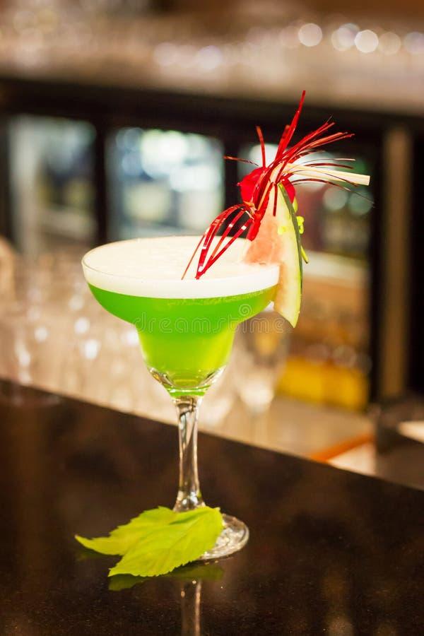 Cocktail alco?lico verde com hortel? em um vidro do margarita em um contador da barra imagem de stock