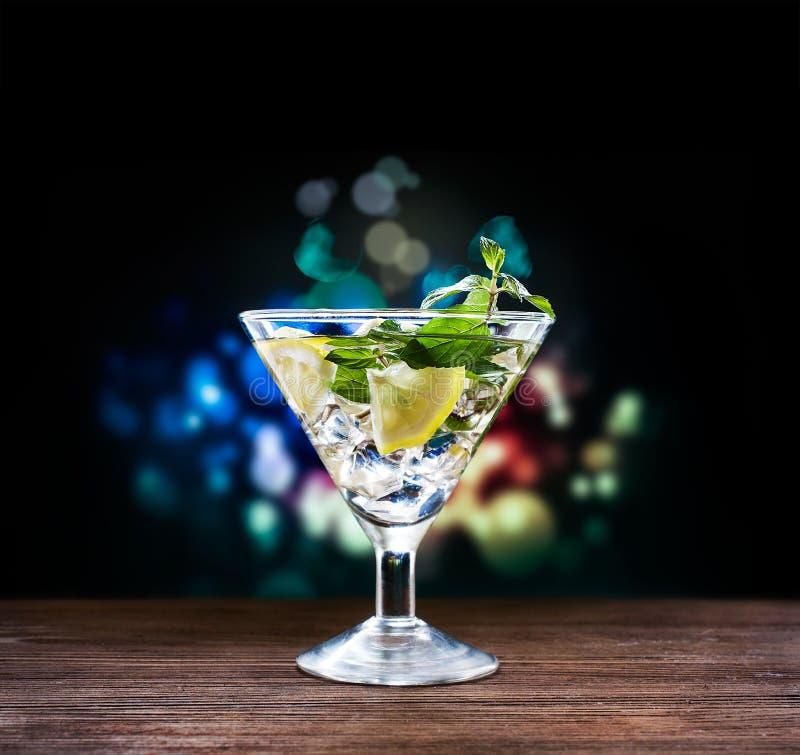 Cocktail alcolico con il limone e la menta in un vetro di martini fotografia stock libera da diritti