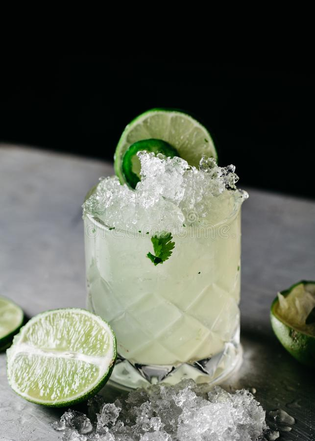 Cocktail alcolico di estate con ghiaccio tritato guarnito con le calce fotografia stock