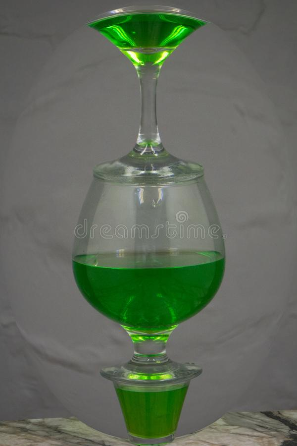 Cocktail alcolico verde fatto di vodka e di liquore con Apple e la fragola Su fondo bianco fotografia stock