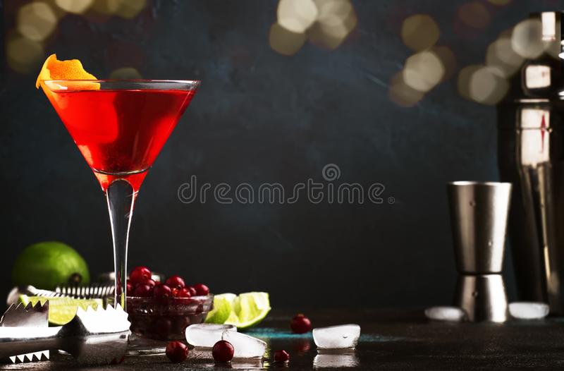 Cocktail alcoolique classique cosmopolite avec la vodka, la liqueur, le jus de canneberge, la chaux, la glace et l'entrain orange images stock