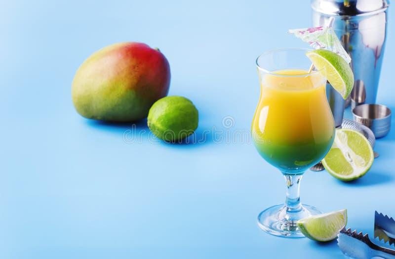 cocktail alcoolique de Deux-couche avec du jus de mangue, le rhum, la liqueur, la chaux et la glace, fond bleu d'?t?, endroit pou photos stock