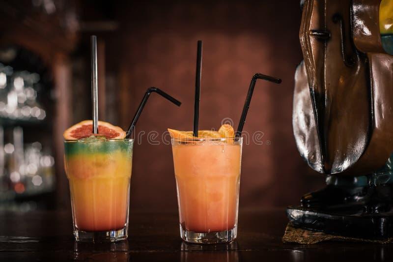 Cocktail alcoolique de deux fruits avec la paille à la table de barre photo stock