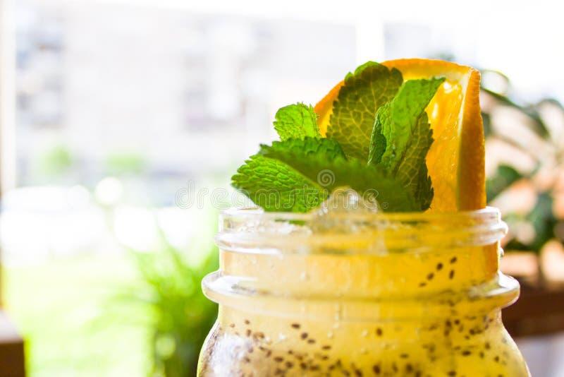 Cocktail analcolico giallo tropicale fresco in un barattolo di muratore decorato con la fetta di arancia e di menta piperita - be immagini stock