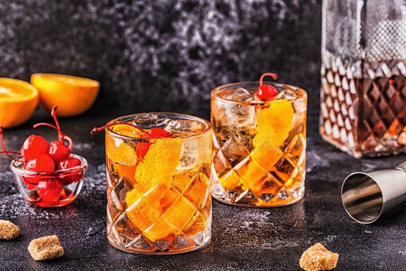 Cocktail antiquato con ciliegie e torsione arancione immagini stock