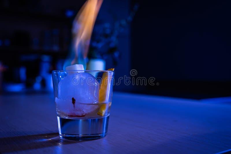 Cocktail antiquato sulla palla di ghiaccio con lo zucchero di combustione fotografie stock libere da diritti