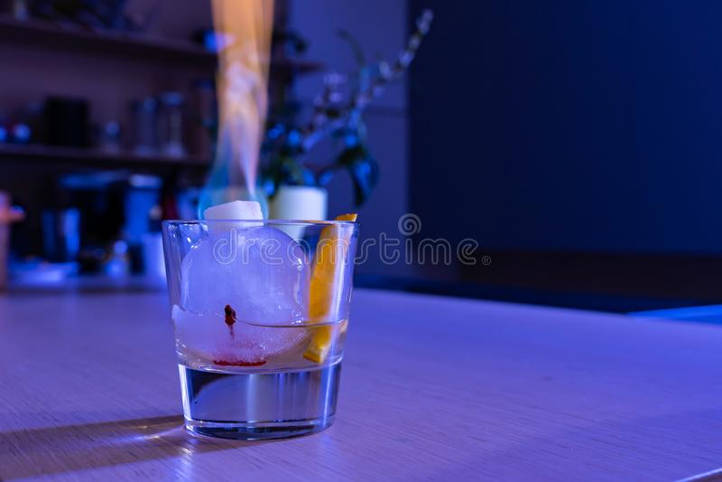 Cocktail antiquato sulla palla di ghiaccio con lo zucchero di combustione immagini stock libere da diritti