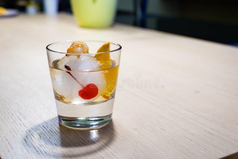 Cocktail antiquato sulla palla di ghiaccio con lo zucchero di combustione fotografia stock