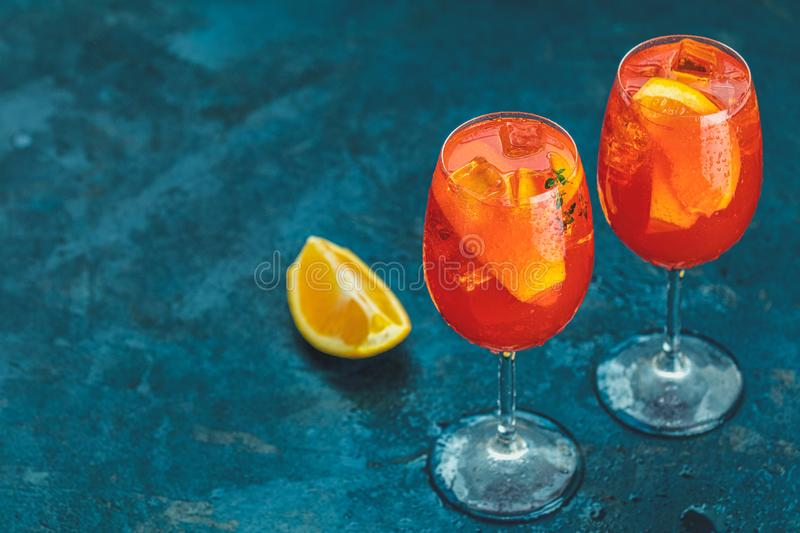 Cocktail aperol spritz in big wine glass with water drops on dark blue background. Summer Italian fresh alcohol cold drink. Selective focus, bar, holiday royalty free stock photo