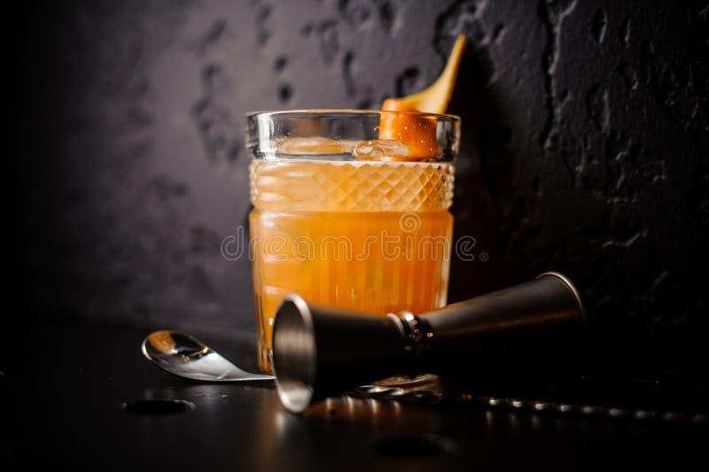 Cocktail arancio in di cristallo con il cucchiaio ed il jigger della barra fotografia stock libera da diritti