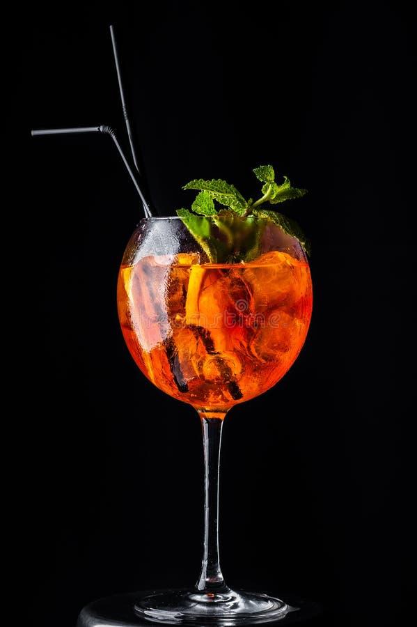 Cocktail arancio in un vetro su un'alta gamba con ghiaccio e la menta, coperti di gocce di rugiada fotografia stock libera da diritti